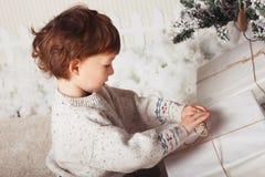 Милый мальчик сидит с подарком около рождественской елки Ребенок счастлив с подарком Нового Года кавказско стоковые фотографии rf