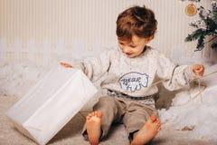Милый мальчик сидит с подарком около рождественской елки Ребенок счастлив с подарком Нового Года кавказско стоковая фотография rf