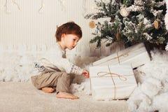 Милый мальчик сидит с подарком около рождественской елки Ребенок счастлив с подарком Нового Года кавказско стоковое изображение rf