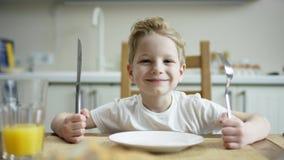 Милый мальчик сидя на таблице с ножом и вилкой и ждать другую семью для того чтобы иметь камеру заскока еды сток-видео