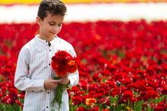 Милый мальчик с букетом лютиков в весеннем времени стоковая фотография