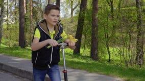 Милый мальчик с букетом цветков ехать на самокате пинком в парке видеоматериал