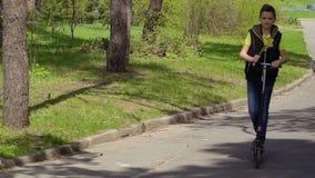 Милый мальчик с букетом narcissus едет на самокате пинком в парке сток-видео