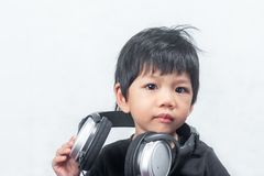 Милый мальчик с наушниками на белой предпосылке стоковое изображение