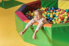 милый мальчик усмехаясь на камере пока играющ в бассейне с красочным стоковое изображение rf