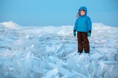 Милый мальчик outdoors играя на пляже зимы стоковые фото