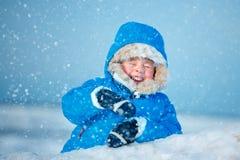 Милый мальчик outdoors играя на пляже зимы стоковое изображение
