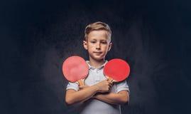 Милый мальчик redhead одел в владениях белых футболки 2 ракетки пингпонга в пересеченных руках на текстурированной темноте Стоковые Фото