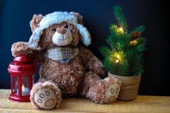 Милый медведь игрушки держа лапку на красном фонарике на черной предпосылке В рамке, вы можете увидеть небольшую рождественскую е стоковые изображения