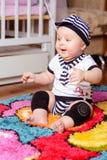 Милый младенец в striped рубашке и шляпах усаженных на циновку в комнате стоковая фотография rf