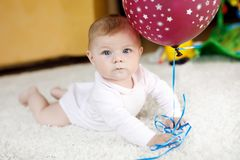 Милый младенец играя с красным воздушным шаром Ребенок, маленькая девочка имея потеху, хватать и вползать новорожденного Семья, н стоковые фотографии rf