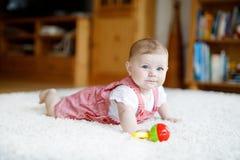Милый младенец играя с красочной игрушкой образования трещотки Девушка Lttle смотря камеру и вползать Семья, новая жизнь стоковое изображение rf