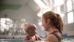 Милый младенец имея плавая урок с его матерью Здоровая мать уча, что их младенец поплавал в бассейне r видеоматериал