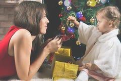 Милый младенец и мама украшая рождественскую елку шарики красные Стоковая Фотография