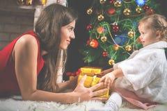 Милый младенец и мама украшая рождественскую елку шарики красные Стоковые Фотографии RF