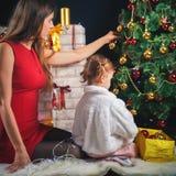 Милый младенец и мама украшая рождественскую елку шарики красные Стоковые Фото
