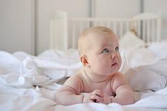 Милый младенец лежит в кровати стоковые изображения
