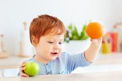 Милый младенец малыша redhead держа свежие плодоовощи яблока и апельсина Стоковые Фото