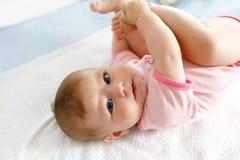 Милый младенец принимая ноги в рте Прелестный маленький ребёнок всасывая ногу Стоковое Изображение