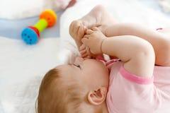Милый младенец принимая ноги в рте Прелестный маленький ребёнок всасывая ногу Стоковое Изображение RF