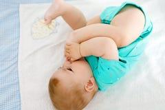 Милый младенец принимая ноги в рте Прелестный маленький ребёнок всасывая ногу Стоковое фото RF