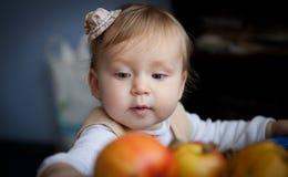 Милый младенец смотрит на сочных красных яблоках Маленькая девочка достигая вне для яблока стоковое фото