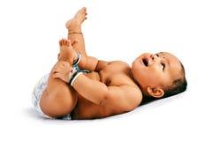 Милый младенец спать на кровати держа его ноги и смеясь, Пуна, махарастра стоковая фотография