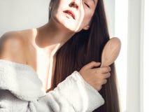 Милый, молодая женщина расчесывая ее волосы стоковые фотографии rf