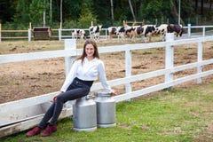 Милый молодой взрослый фермер девушки, сидя дальше может после работы Большая чонсервная банка 2 с молоком Перерыв после работы в Стоковая Фотография RF