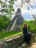 Милый молодой женский турист представляя перед руинами Tikal, старыми майяскими руинами глубоко в тропических лесах северной Гват стоковое изображение rf