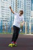 Милый молодой мальчик спорта катаясь на коньках на желтом скейтборде и имеет полезного время работы на его свободном времени на в стоковое фото