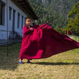 Милый молодой монах послушника позволил его робе порхая в ветре, восточном Бутане стоковые фотографии rf