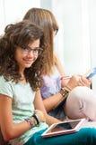 Милый молодой студент сидя с таблеткой. Стоковое Изображение