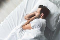Милый молодой человек спать на кровати стоковое изображение