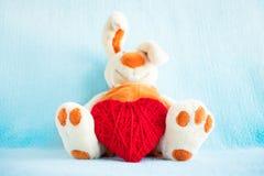 Милый мягкий кролик и красный цвет игрушки связали сердце на голубой предпосылке Стоковое Фото