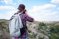 Милый парень и фотографируя с камерой Пеший туризм в горах с камерой Самое лучшее времяпровождение в лете стоковая фотография rf