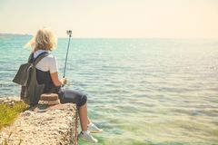 Милый портрет selfie взятий туриста молодой женщины на seashore на девушке солнечного дня принимает фото для блога перемещения Вз Стоковые Изображения