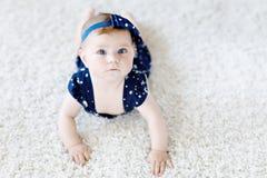 Милый прелестный ребёнок в голубых одеждах и держателе Ребенок новорожденного, маленькая девочка смотря камеру и вползать стоковое изображение