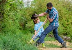 Милый ребенок в природе имея папы ковбоя потехи Найдите сокровища Мальчик и отец с лопаткоулавливателем ища сокровища стоковое изображение
