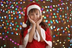 Милый ребенок в шляпе Санты на запачканной предпосылке светов отпразднуйте носить santa мати шлемов дочи рождества торжества Стоковое Изображение RF