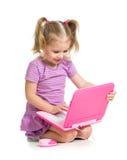 Милый ребенок играя на компьтер-книжке на белой предпосылке Стоковая Фотография