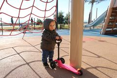 Милый ребенок играя со скутером 3 колес стоковое фото