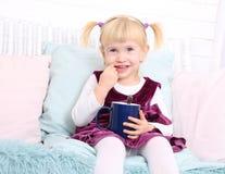 Милый ребенок сидит в стуле и ест печенья стоковые изображения