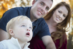 Милый ребенок смотрит до небо по мере того как молодые родители усмедутся Стоковая Фотография RF