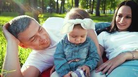 Милый ребенок с родителями на зеленой траве в парке лета с пирофакелом объектива акции видеоматериалы