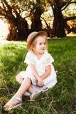 Милый ребёнок в соломенной шляпе и платье белизны сидит на траве стоковые изображения