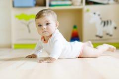 Милый ребёнок уча вползать и сидеть в комнате детей стоковое фото rf