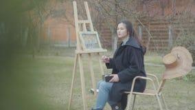 Милый сконцентрированный художник маленькой девочки сидя перед деревянным мольбертом рисуя изображение Женский художник в случайн сток-видео