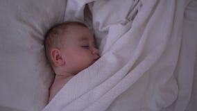 Милый спать младенец лежа под белым одеялом в замедленном движении акции видеоматериалы