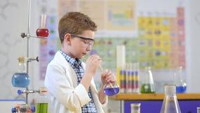 Милый старт мальчика эксперимент с жидкостью в лаборатории акции видеоматериалы